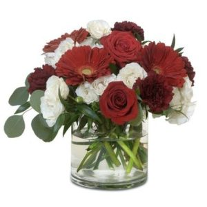 omantic blooms of ivory, and passionate reds fill the centerpiece for a delicious display. We love the deep burgundy mixed with the bright red roses and gerberas for a simply wonderful piece.